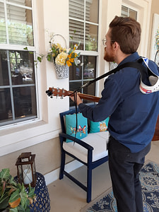 Tidewell music therapist Michael Russo provides a session through a window at an assisted living facility during pandemic